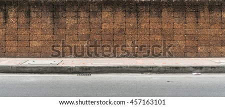 Laterite block fence and concrete sidewalk and asphalt road - stock photo