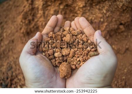 laterite soil on hand - stock photo