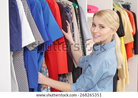 Latest fashionable trends. Young beautiful blond woman choosing clothes in a fashionable boutique