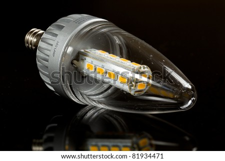 Latest LED light bulb in candle shape and reflecting off a black surface - stock photo