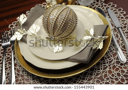 Latest trend of gold metallic theme Christmas  formal dinner table place setting with fine bone china, bauble and festive decorations. Close up. - stock photo