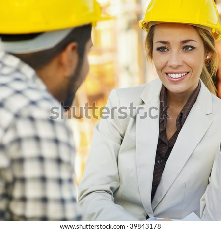 latin american construction worker and female architect talking. - stock photo