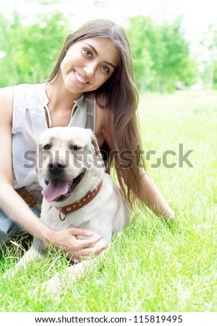 Latin American girl embraces her dog in the park on the background of green grass