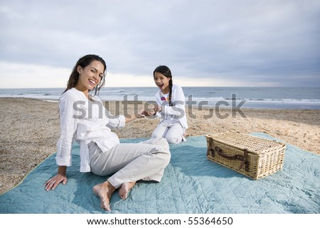Latin American mother and 9 year old girl having picnic on beach - stock photo