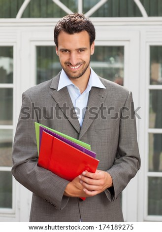 Latin businessman with paperwork in front of his office   - stock photo