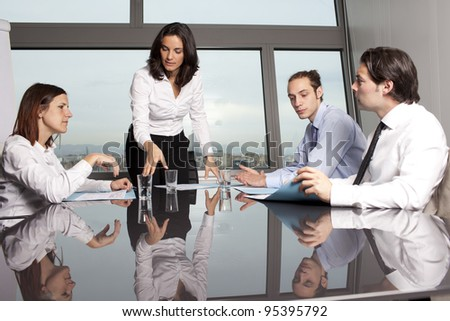latin businesswoman in an office with her team in an office - stock photo
