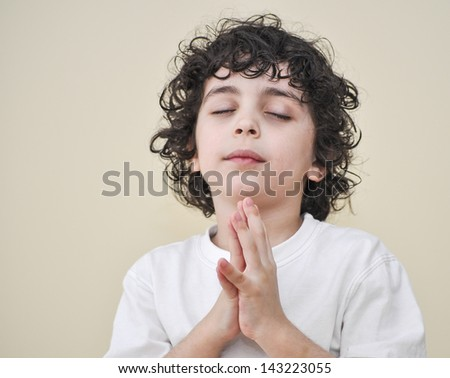 Latin child in humble communication through prayer with his Creator in heaven - stock photo