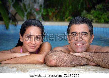 Latin couple enjoying together in a swimming pool. - stock photo