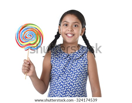 Latin female child holding huge lollipop happy and excited wearing cute blue dress and pony tails standing isolated on white background in kid loving candy and sweet sugary food concept - stock photo