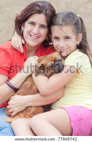 Latin girl and  her mother hugging the family dog and sitting on the grass outdoors