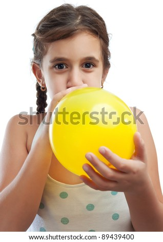Latin girl blowing a yellow balloon isolated on a white background - stock photo