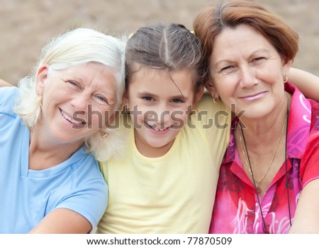 Latin girl hugging her two grandmothers and smiling - stock photo