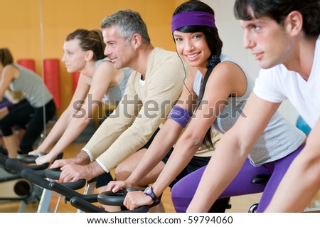 Latin girl smiling and looking at camera while exercising with bicycles in group at gym