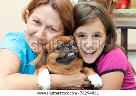 Latin grandmother and granddaughter hugging the family dog - stock photo
