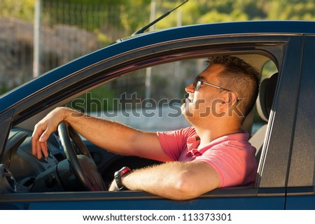 Latin guy inside his car trying to look cool - stock photo