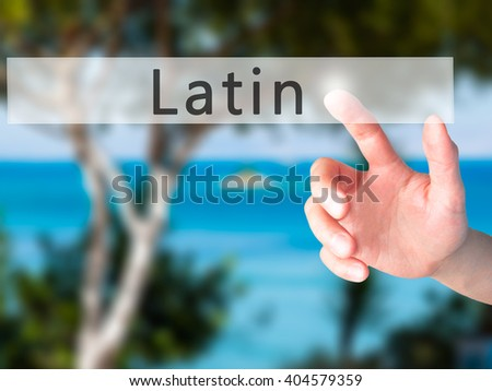 Latin - Hand pressing a button on blurred background concept . Business, technology, internet concept. Stock Photo