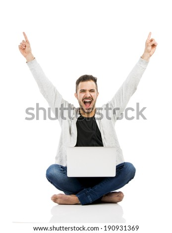Latin man sitting on the floor and working with a laptop with both arms up - stock photo