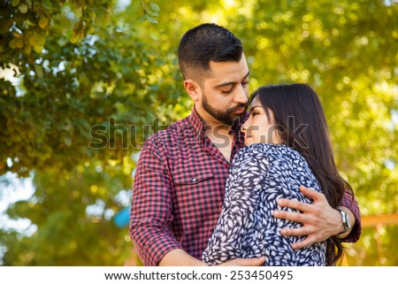 Latin man with a beard embracing his girlfriend and looking at her - stock photo