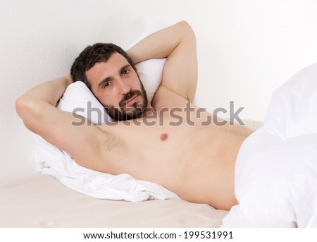 latin man with naked torso lying in bed