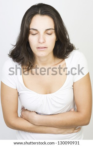 latin mid-adult woman with stomachache - stock photo