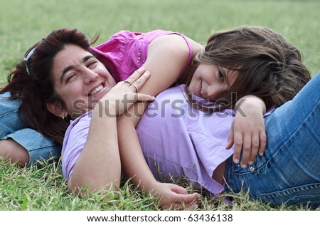Latin mother and daughter lying down and smiling in a green grass field - stock photo