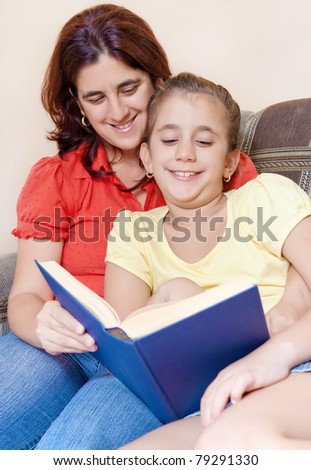 Latin mother and daughter reading a book together