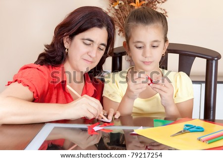 Latin mother and daughter working on an art project at home with some art supplies on the table - stock photo