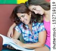 Latin mother and her beautiful teenage daughter reading a book at home - stock photo