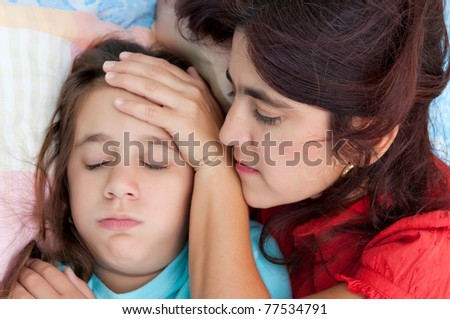 Latin mother checking the temperature of  her sick coughing daughter in bed - stock photo