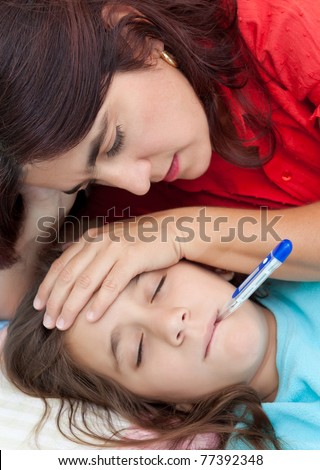 Latin mother checking the temperature of  her sick daughter who has a thermometer in her mouth - stock photo