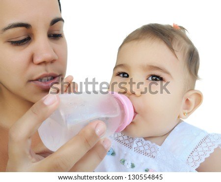 Latin mother giving water in a baby bottle to her thirsty daughter isolated on white - stock photo