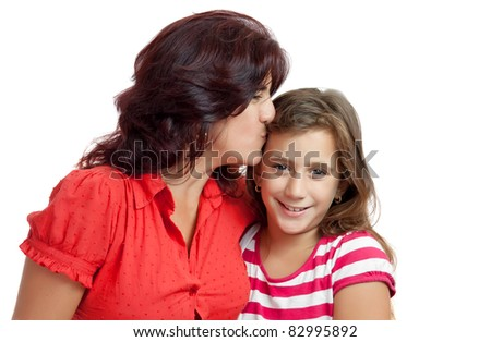 Latin mother kissing her daughter isolated on a white background
