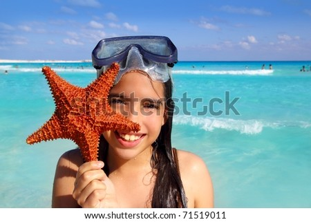 latin tourist girl holding starfish in tropical beach - stock photo
