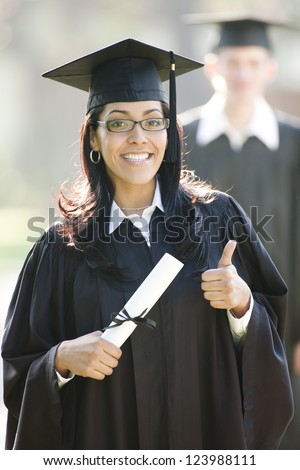 Latin woman graduate with thumbs up in graduation cap and gown and diploma - stock photo