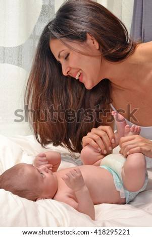 Latin woman sharing with her baby born on bed.Enjoying my baby boy Parent and little kid relaxing at home. Family having fun together. Bedding and textile for infant nursery.