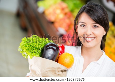 Latin woman shopping for groceries at the marketplace - stock photo