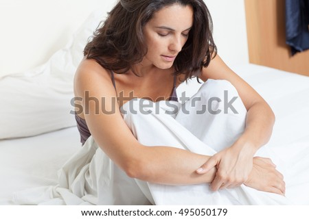 Latin woman with stomach ache sitting in bed