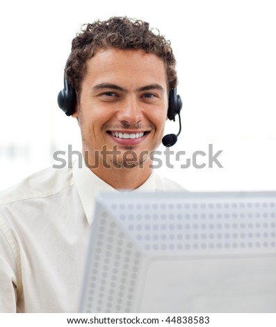 Latin young businessman with headset on working at a computer - stock photo