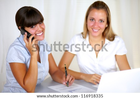 Latin young businesswoman talking on cellphone at the office while is looking at you with a colleague