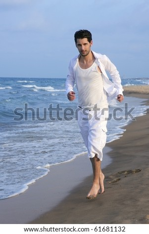 Latin young man white shirt walking on blue beach outdoor