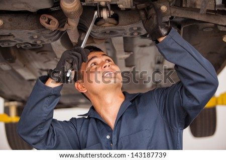 Latin young mechanic working on a suspended car at an auto shop - stock photo