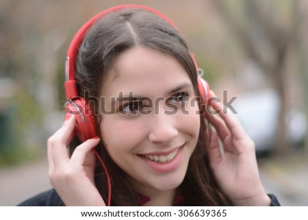 Latin young woman listening to music with red headphones. - stock photo