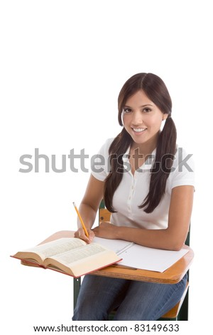 Latina High school or college female student sitting by the desk at class doing homework.