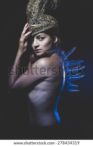 latina naked warrior with a golden helmet and armor methacrylate - stock photo