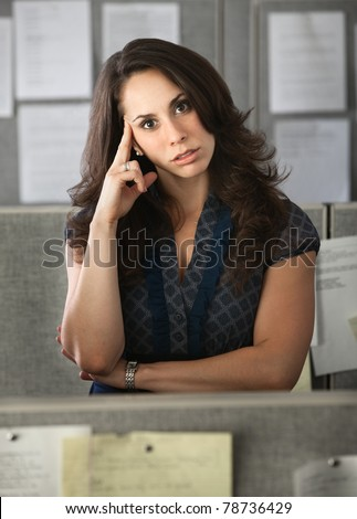 Latina office worker in a cubicle with hand on head - stock photo