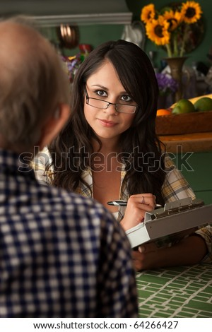 Latina social worker or home care provider with elderly man - stock photo