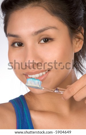 Latina teenager girl brushes her teeth - stock photo