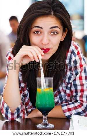 Latina woman drinking cocktail with straw in a bar.