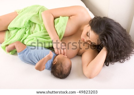 Latina woman lying on bed and breastfeeding her 2 months old baby of mixed Hispanic and African-American ethnicity