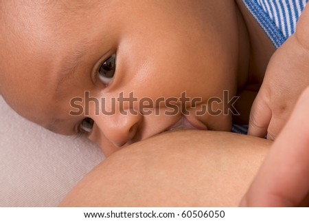 Latina woman lying on bed and breastfeeding her 2 months old baby of mixed Hispanic and African-American ethnicity - stock photo